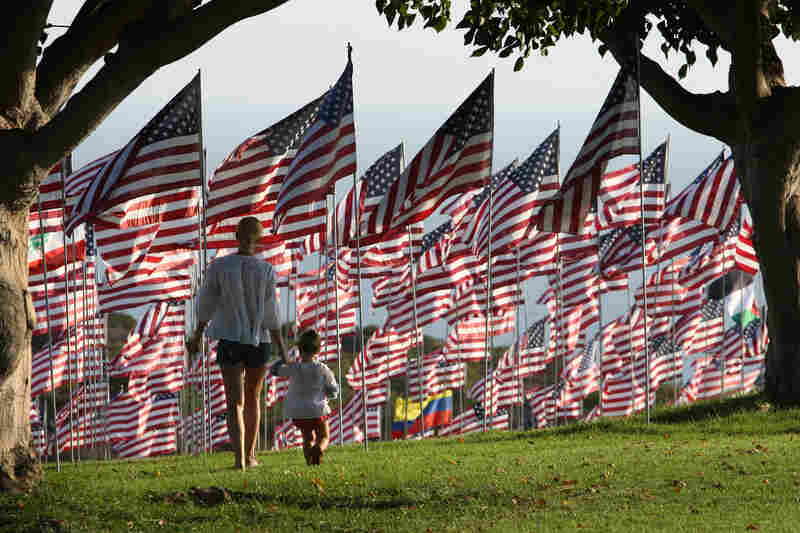 Dominique Sanders walks Monday with her daughter Roux, 2, among flags flying at Pepperdine University in Malibu, Calif., in honor of the victims of the Sept. 11 attacks. One flag from the nationality of each person killed that day was erected at the school.