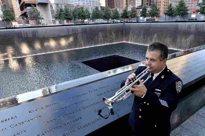 New York City police bugler Gabe Perdomo warms up next to the South Pool at ground zero during Tuesday's memorial ceremonies for the 11th anniversary of the Sept. 11 attacks.
