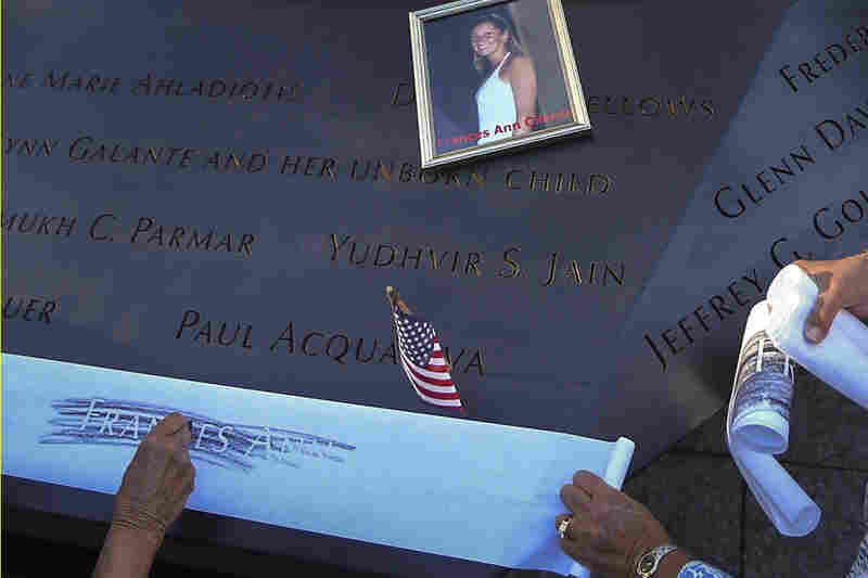 Judy Parisio (right) and Linda Malbrba make a rubbing of their niece's name, Frances Ann Cilente, who worked at the World Trade Center, during ceremonies marking the anniversary of the Sept. 11 attacks.