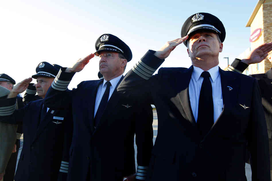 Airline pilots Capt. Anthony Chapman (right) and Capt. Paul Evans salute with others as the U.S. flag is lowered to half staff at the 9/11 Flight Crew Memorial in Grapevine, Texas. Flight crews gathered at the memorial near Dallas-Fort Worth airport to remember the flight