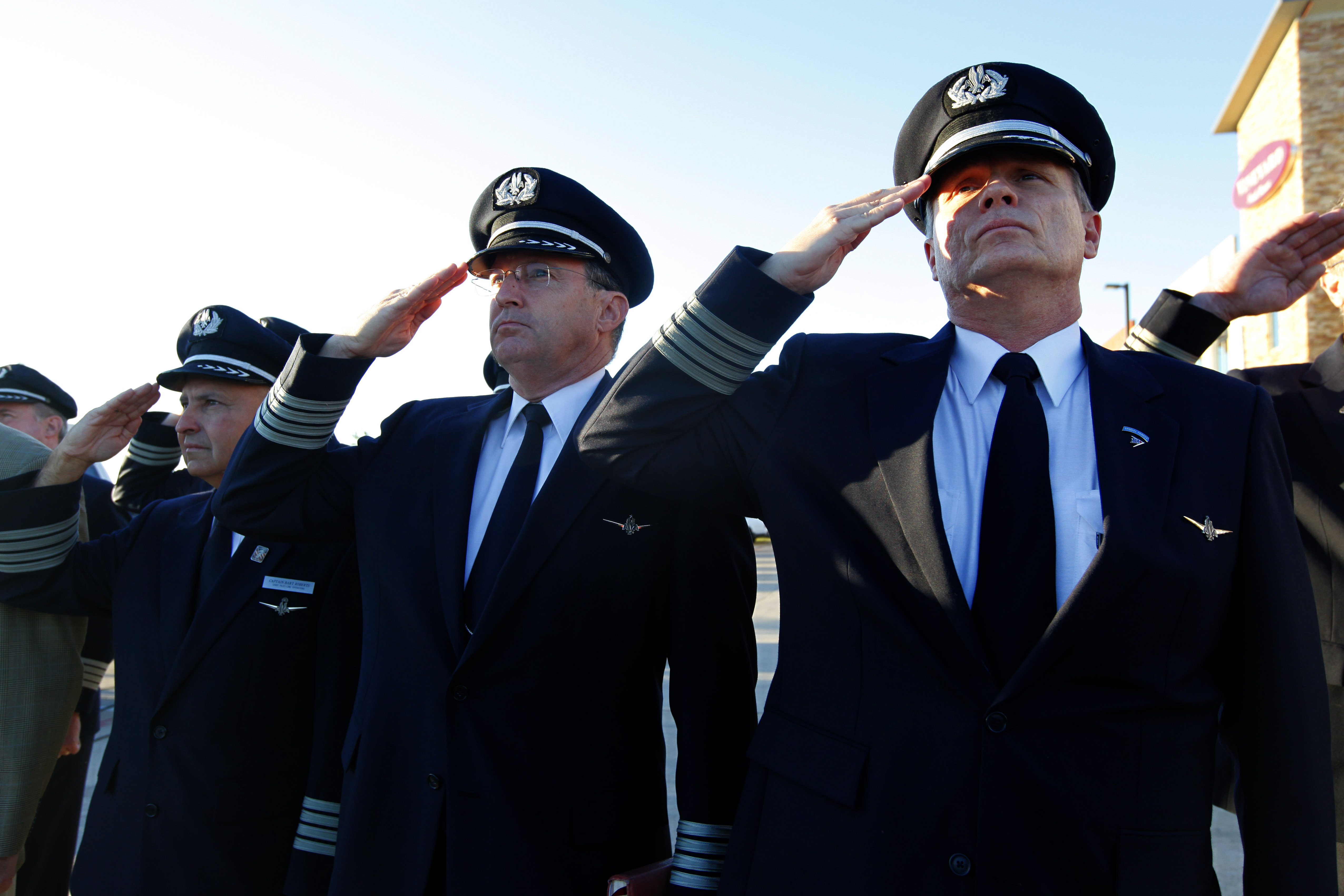 Airline pilots Capt. Anthony Chapman (right) and Capt. Paul Evans salute with others as the U.S. flag is lowered to half staff at the 9/11 Flight Crew Memorial in Grapevine, Texas. Flight crews gathered at the memorial near Dallas-Fort Worth airport to remember the flight crews lost in the Sept. 11 attacks.