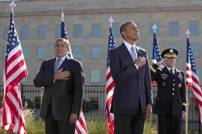 President Obama stands with Defense Defense Leon Panetta (left) and Joint Chiefs Chairman Gen. Martin Dempsey, as they place their hands over their hearts at the Pentagon Memorial,Tuesday, during a ceremony to mark the 11th anniversary of the Sept. 11 attacks in Arlington, Va.
