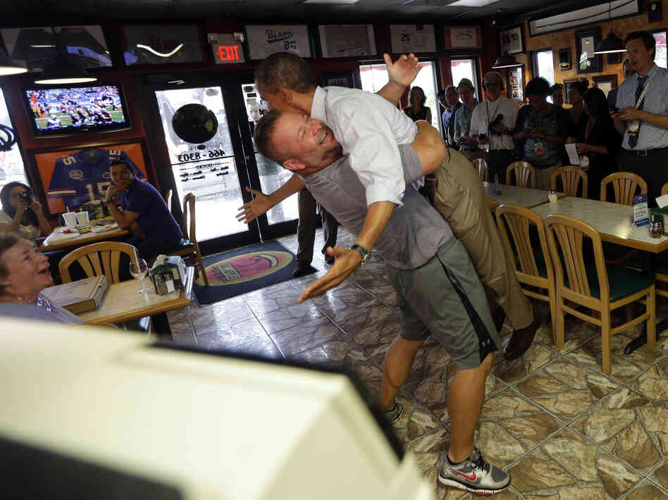 President Obama is lifted off the ground by Scott Van Duzer, owner of Big Apple Pizza and Pasta Italian Restaurant, during an unannounced stop Sunday in Fort Pierce, Fla.