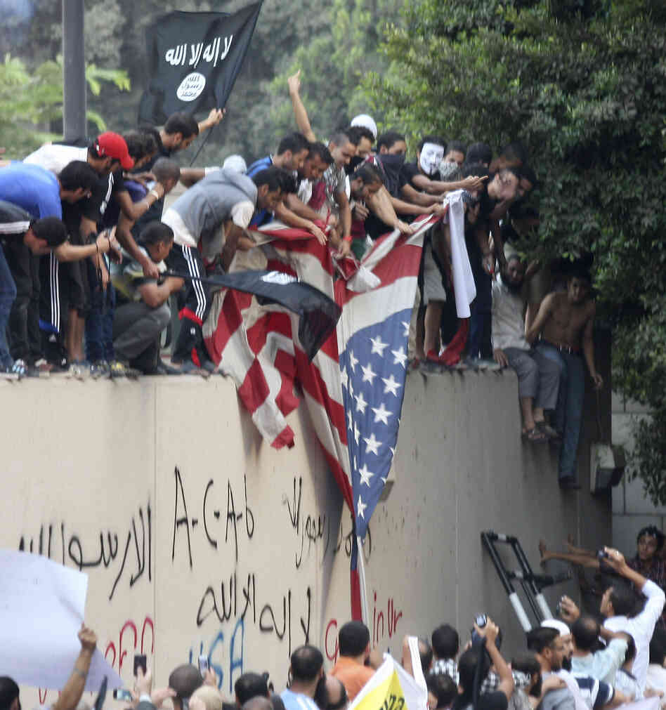 Protesters destroy an American flag pulled down from the U.S. embassy in Cairo, Egypt on Tuesday.
