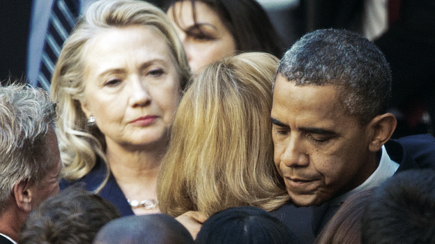 Secretary of State Hillary Clinton looks on as President Obama hugs a State Department employee Wednesday. Obama met with State Department workers after the killing of four Americans in Libya. (AFP/Getty Images)