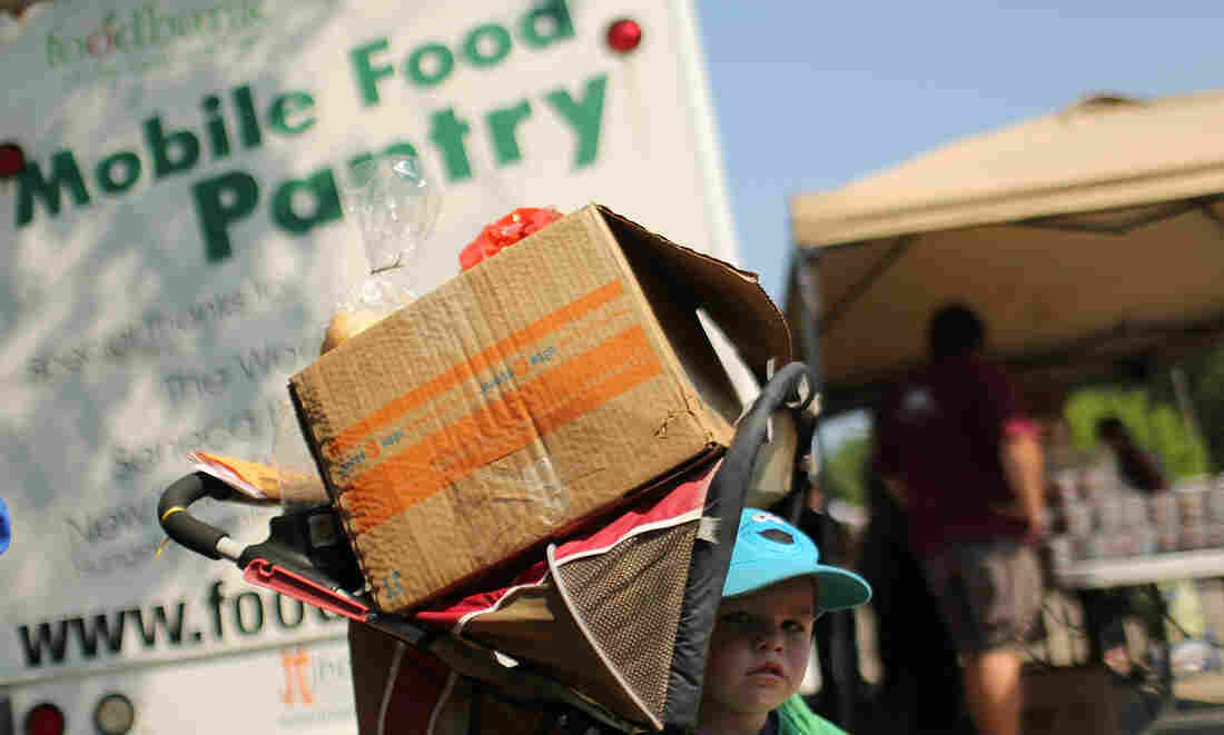 A child waits with a box of food at a mobile food bank in Oswego, N.Y., in June. New census data show that 46.2 million people in the U.S. lived below the poverty line last year.