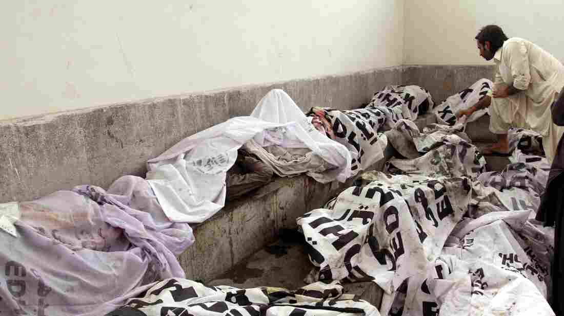 A man tries to identify body of his relative at a mortuary following a huge fire at a garments factory in Karachi, Pakistan.