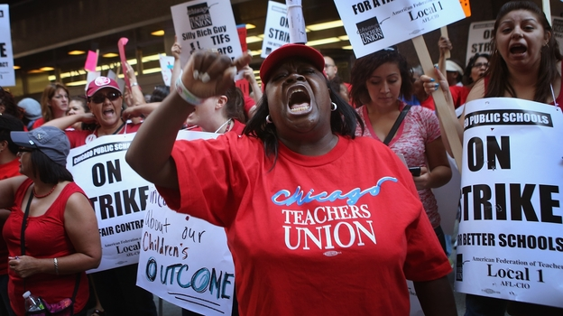 Chicago public school teachers and their supporters picket in front of the Chicago Public Schools headquarters. (Getty Image)