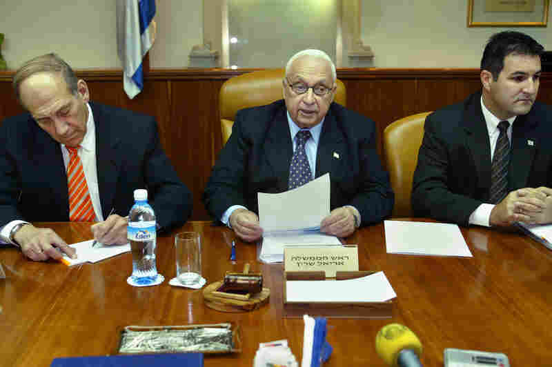 Sharon, flanked by Deputy Prime Minister Ehud Olmert (left) and Cabinet Secretary Yisrael Maimon, reads a statement during the weekly Cabinet meeting at Sharon's office, on June 13, 2004, in Jerusalem.