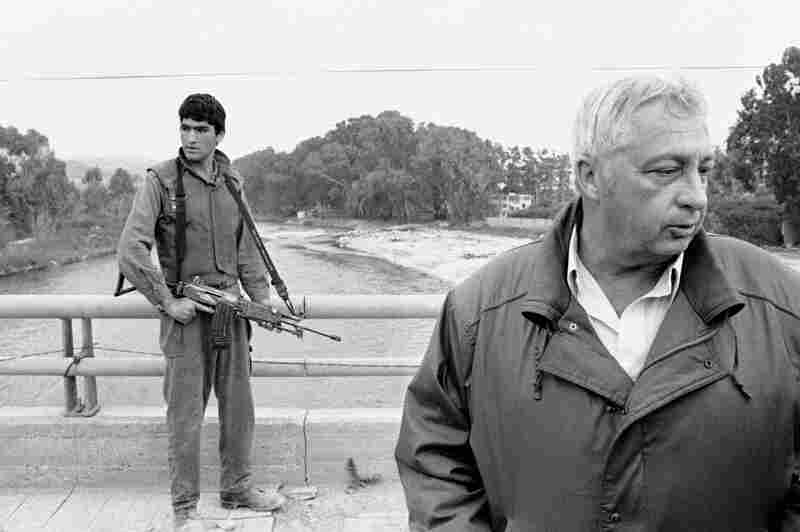 An Israeli soldier keeps his finger on the trigger of his assault rifle while Sharon (right) stands on the bridge overlooking the Awali River, Israel's most northerly position, in Sidon, Lebanon, on March 7, 1984. A few minutes earlier, Sharon had escaped a roadside bomb attack as he was making his way to the bridge.