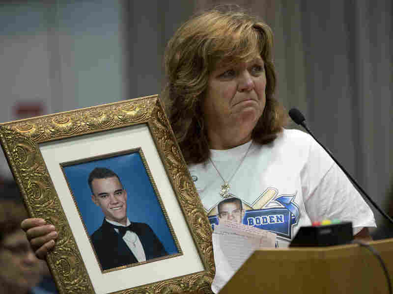 Sandra Boden holds a photo of her son, Jason, during a Task Force on Citizen Safety and Protection hearing. Prosecutors told Boden that Florida's Stand Your Ground law prevented them from filing charges against the person who shot and killed Jason.