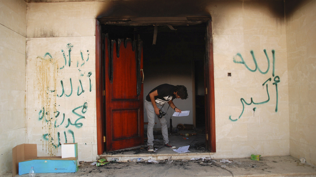 "A man looks at documents at the U.S. Consulate in Benghazi, Libya, on Wednesday, after an attack that killed four Americans, including Ambassador Chris Stevens. The graffiti reads, ""no God but God,"" "" God is great,"" and ""Muhammad is the Prophet."""