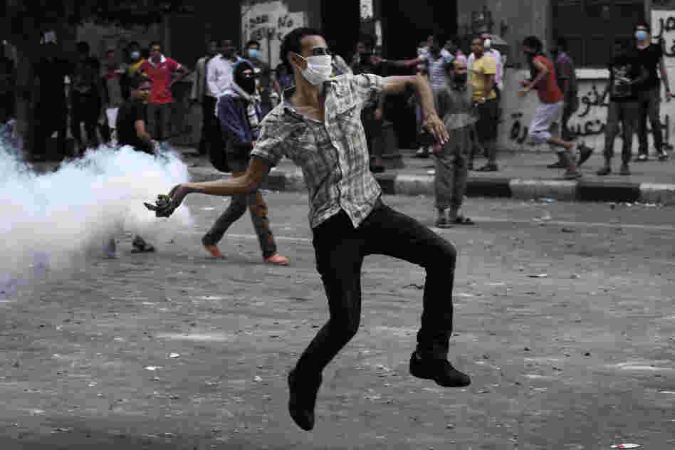 A protester throws a tear-gas canister toward riot police outside the U.S. Embassy in Cairo on Thursday. Dozens were injured in clashes, according to state TV.