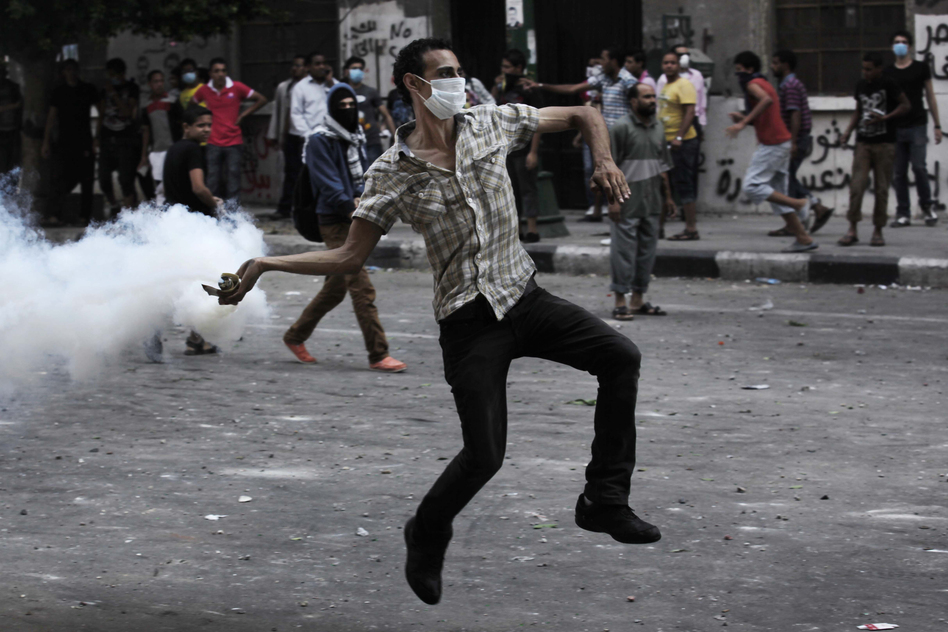 A protester throws a tear-gas canister toward riot police outside the U.S. Embassy in Cairo on Thursday. Dozens were injured in clashes, according to state TV. (AP)