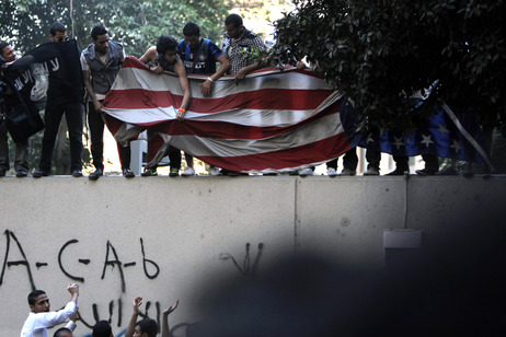 Protesters carry an American flag pulled down from the U.S. embassy in Cairo, Egypt on Tuesday.