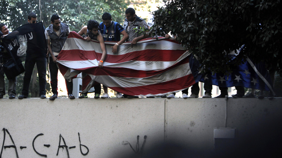 Protesters carry an American flag pulled down from the U.S. embassy in Cairo, Egypt on Tuesday. (AP)