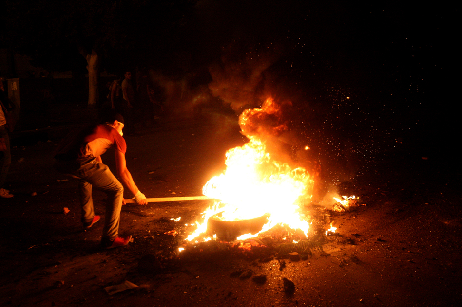 A protester sets a tire on fire during clashes with police in front of the U.S. Embassy in Cairo. (AP)