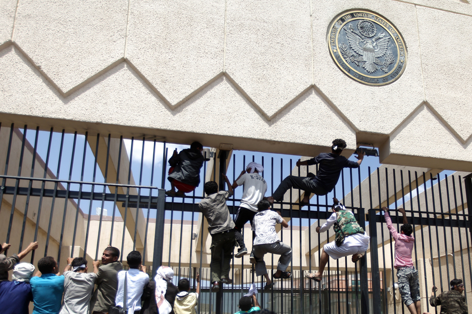 Protesters climb a fence at the embassy as security guards fire warning shots into the air. (Reuters/Landov)