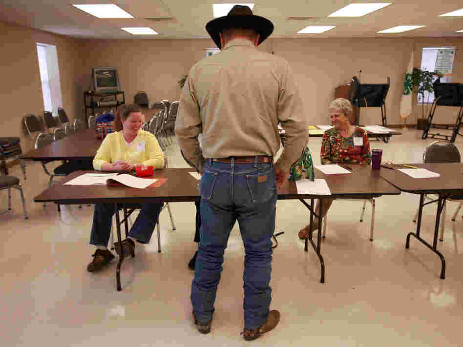 Volunteers check in a voter in Palo Pinto, Texas, in November 2008. The state is using a list from the Social Security Administration to purge dead voters from its election rolls.