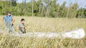 Joe Hoagland, left, pushes a canoe through a wild rice bed as 14-year-o