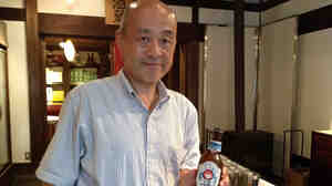 Kiuchi Brewery vice president Youichi Kiuchi holds a bottle of his company's Hitachino Nest beer. To make beer, the brewery is using equipment that once was used for sake.