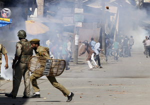 """Kashmiri Muslim protesters throw stones at Indian policemen during a protest in Srinagar, India. The protest was held against an anti-Islam film called """"Innocence of Muslims"""" that ridicules Islam's Prophet Muhammad."""
