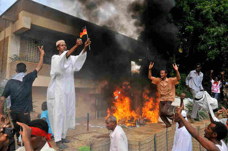 A Sudanese demonstrator burns a German flag as others shout slogans after torching the German embassy in Khartoum during a protest against a low-budget film mocking Islam on Friday. Around 5,000 protesters in the Sudanese capital angry over the amateur anti-Islam film stormed the embassies of Britain and Germany, which was torched and badly damaged.