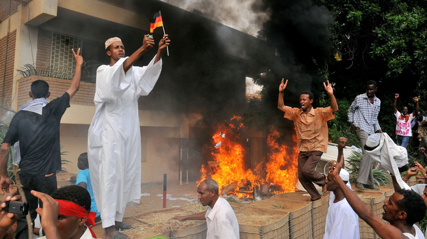 A Sudanese demonstrator burns a German flag as others shout slogans after torching the German embassy in Khartoum during a protest against a low-budget film mocking Islam on Friday. Around 5,000 protesters in the Sudanese capital angry over the amateur anti-Islam film stormed the embassies of Britain and Germany, which was torched and badly damaged. (AFP/Getty Images)