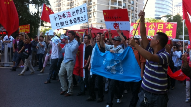 Protesters march outside the Japanese Embassy in Beijing on Saturday. Tension escalated, sometimes to violence, in cities across China after Japan bought the disputed islands from a private Japanese owner. (NPR)