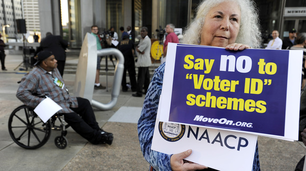Gloria Gilman holds a sign Thursday in Philadelphia  during the NAACP voter ID rally to demonstrate her opposition to Pennsylvania's new voter identification law.