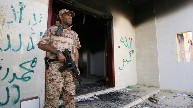 A Libyan military guard stands in front of one of the U.S. Consulate's burnt-out buildings in Benghazi Sept. 14 during the visit of President Mohammed el-Megarif. (AP)