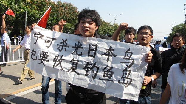 "Protester Mu Peidong carries a homemade sign that reads: ""Even if we have to kill all Japanese, we must recover the Diaoyu islands."" (NPR)"