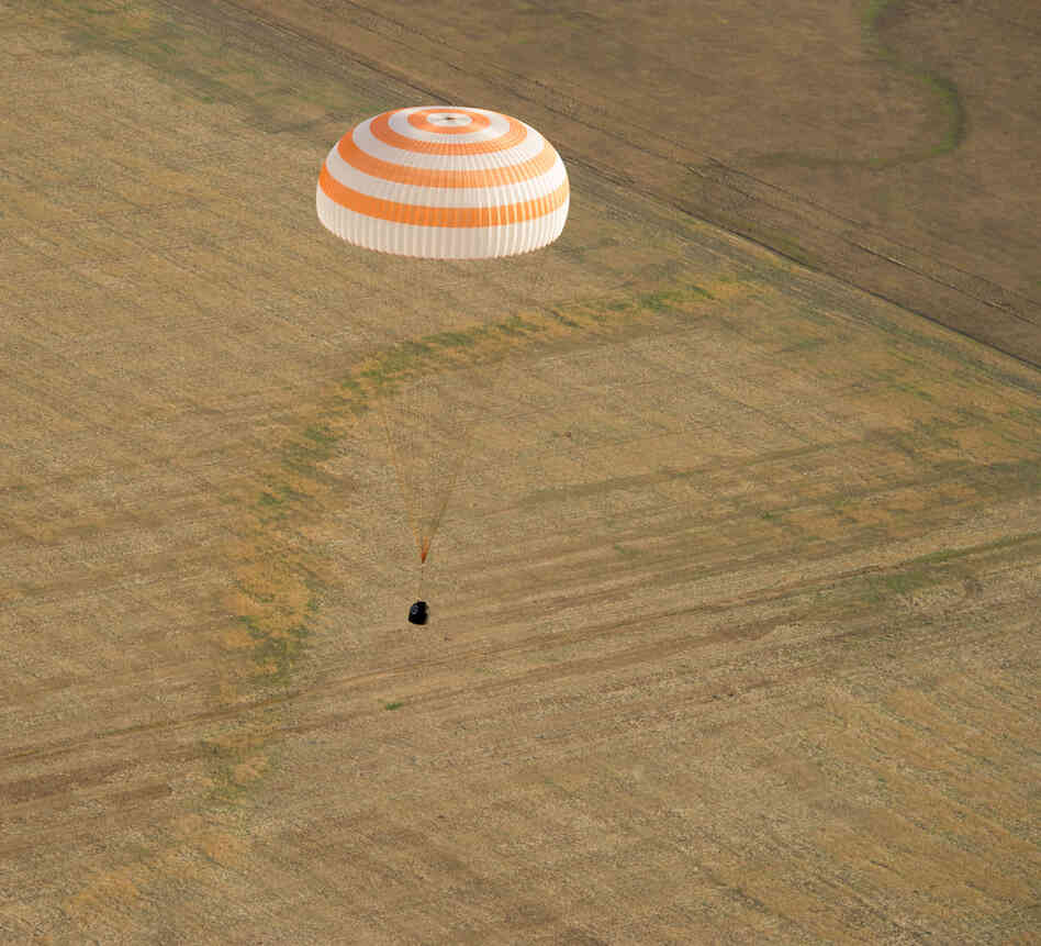 The Soyuz capsule floats as it brings Commander Gennady Padalka of Russia, NAS