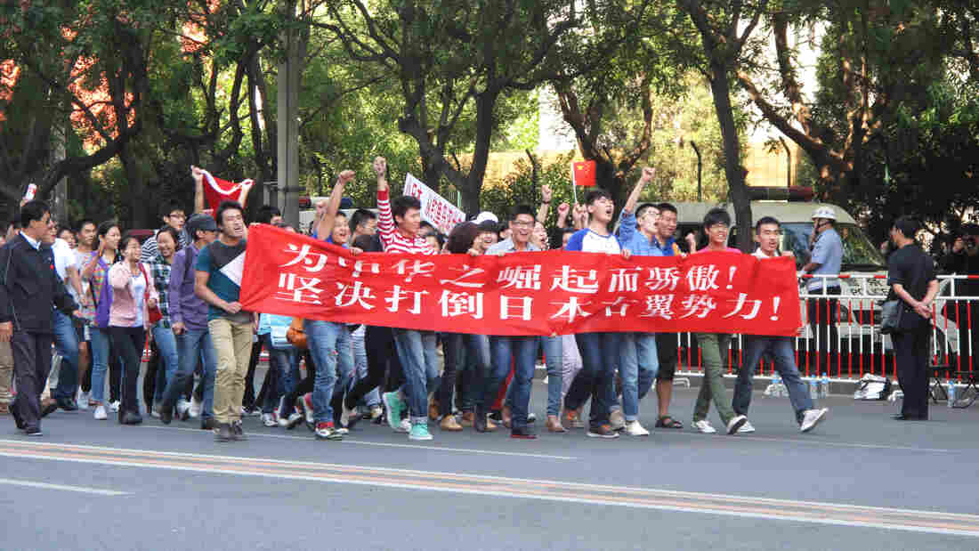 """Protesters marched in front of the Japanese Embassy in Beijing today. They carried a banner declaring: """"We are proud of China's rise. We resolutely oppose Japan's rightist forces."""""""