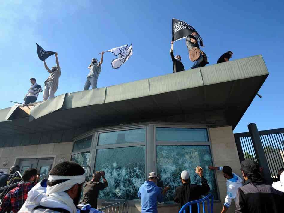 Tunisian protesters break the windows as they hold Islamic flags above the gate of US embassy in Tunis during a protest against a film mocking Islam on September 14, 2012.