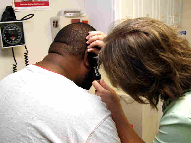 A Unity Health Care patient gets his ears checked.