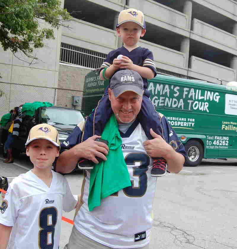 "Rowdy Smith, who brought his sons to the St. Louis Rams game on Sunday, said that President Obama's ""not a leader"" and is hurting the energy industry. He's shown here walking in front of the Americans for Prosperity campaign bus."