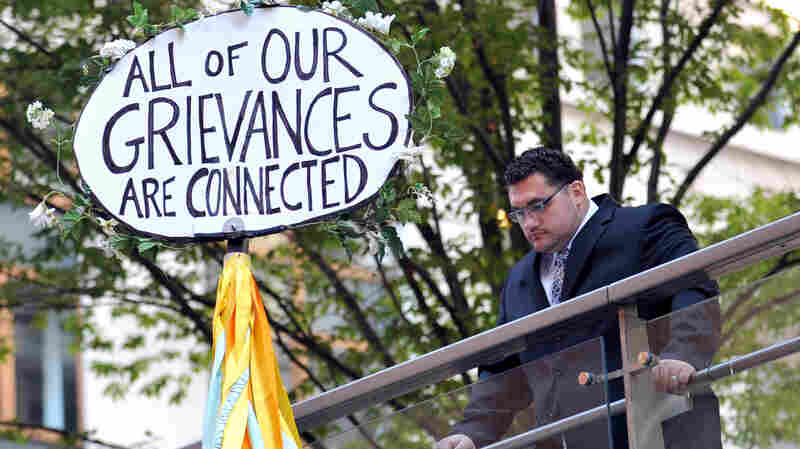 A man looks down at a sign during the Occupy Wall Street protest on the one year anniversary of the movement in New York.