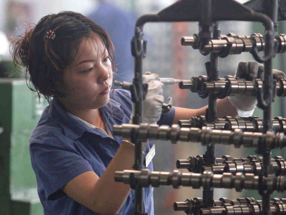 A worker inspects auto parts at a factory in Chengdu, China. (2005 file photo.)