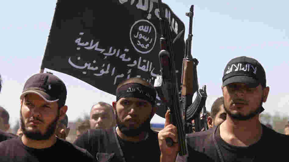 Islamist fighters carry their flag during the funeral of a fellow fighter who died during clashes on Sunday, outside Aleppo in northern Syria. A similar flag, raised over the Bab al-Hawa border crossing, was at the heart of a dispute that highlights the growing tension between homegrown Syrian rebels and radical Islamists who have flowed into the country.