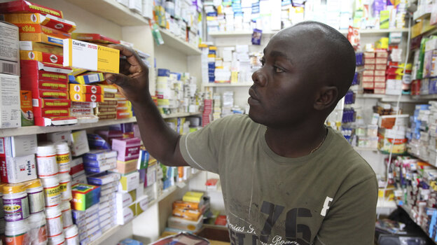 Ayo Bello grabs a box of malaria medication at a pharmacy in Lagos, Nigeria. A pilot project by the Global Fund has helped private pharmacies