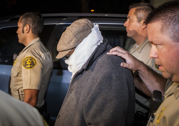 Los Angles County Sheriff's officers escort an unidentified person out of Nakoula Basseley Nakoula's home in Cerritos, Calif., early Saturday.