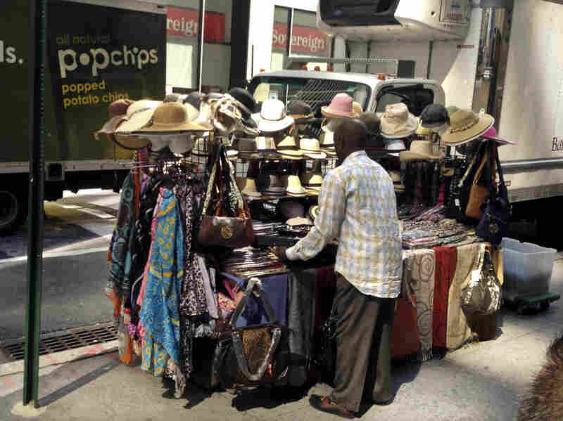 """Cheikh Fall sets up his stall. He lives by the motto, """"Work like you're never gonna die, and worship like you will die tomorrow."""""""