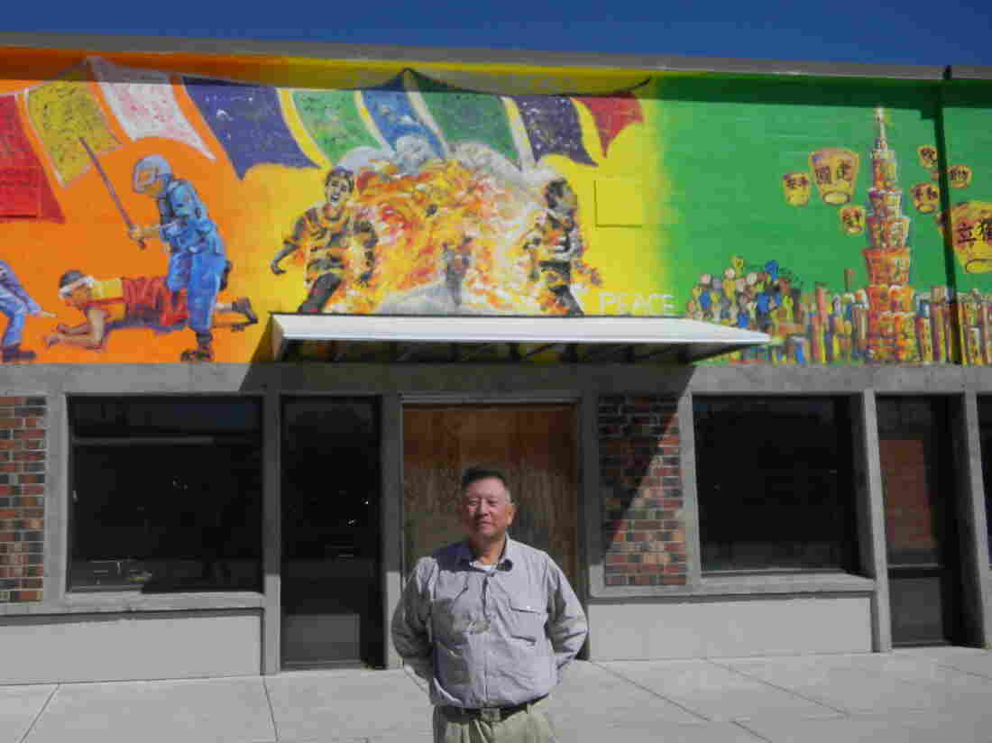 Businessman David Lin stands in front of a mural depicting a self-immolating monk he commissioned in Corvallis, Ore. The Chinese consulate in San Francisco sent a letter to Corvallis' mayor requesting the mural's removal.