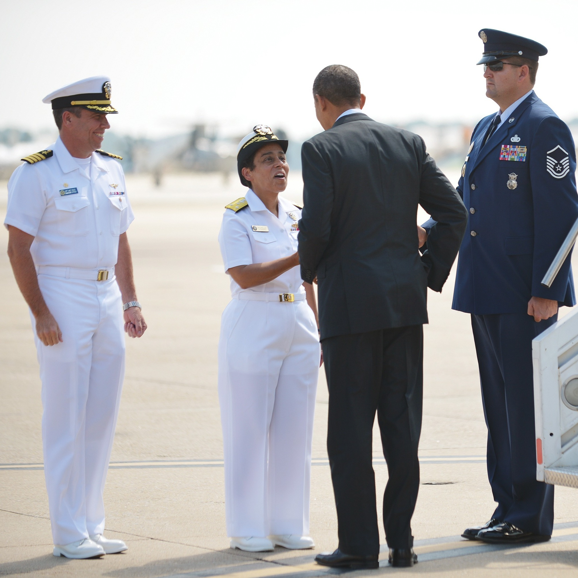 President Obama is greeted by naval officers at Naval Air Station Norfolk, in Norfolk, Va., on Sept. 4.