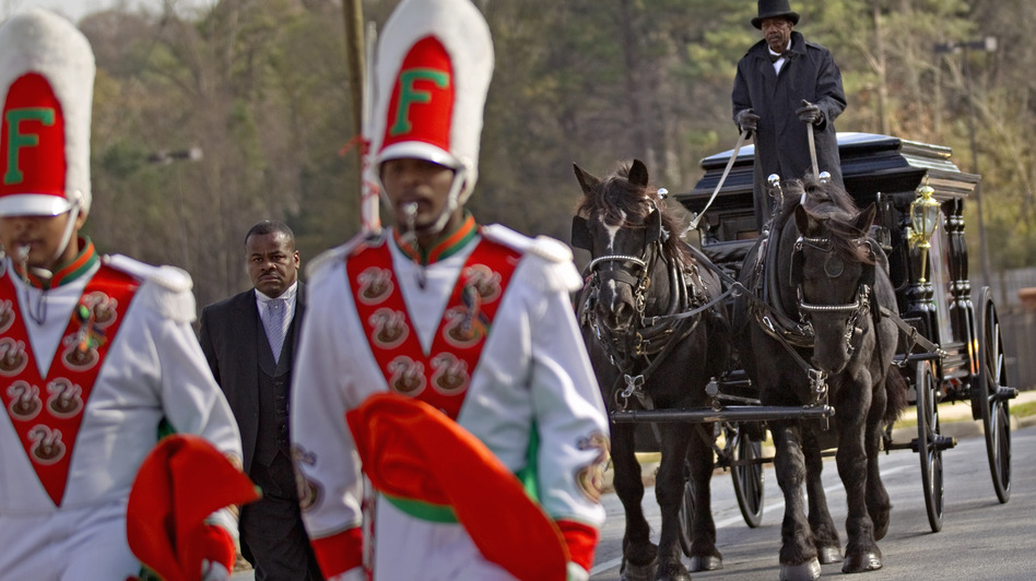 A horse-drawn carriage carrying the casket of Florida A&M University band member Robert Champion is led by his fellow band members following his funeral service in November. (AP)