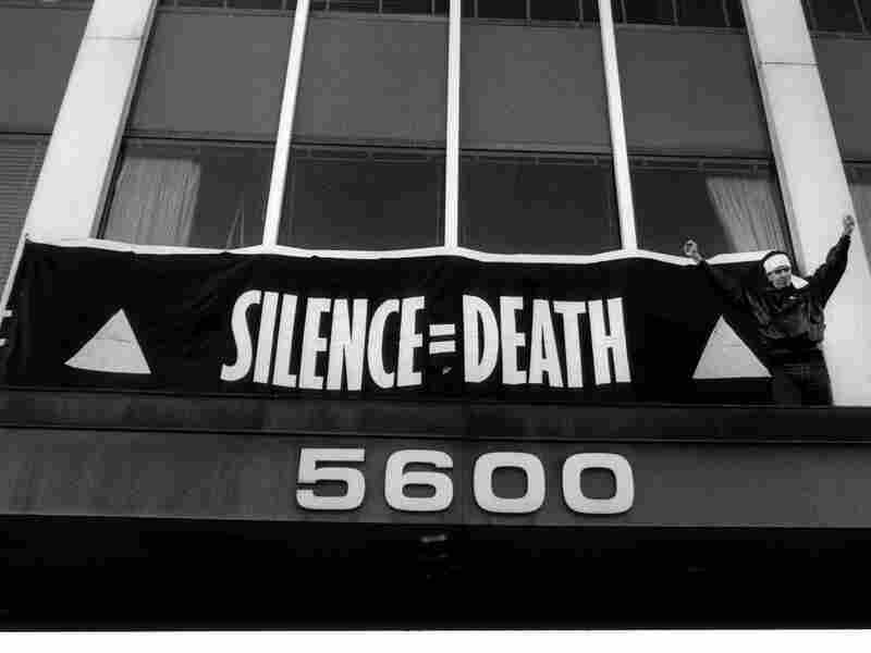 "Staley hangs a banner bearing ACT UP's signature ""Silence = Death"" slogan over the main entrance of FDA headquarters in October 1988."