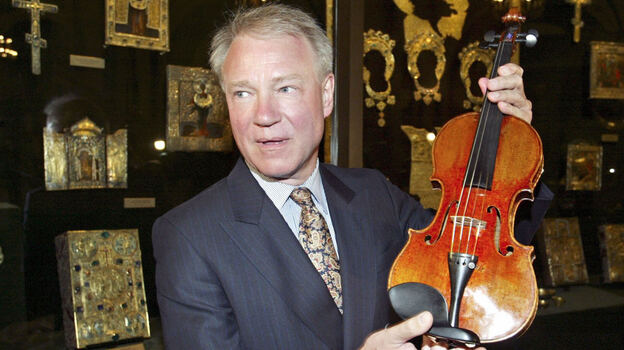 Con man/violin dealer Dietmar Machold holds a (purported) Strad in Moscow in 2003. (AFP/Getty Images)