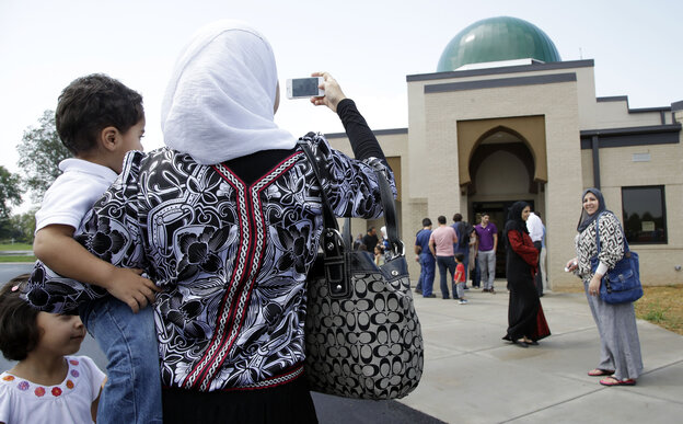 A woman takes a picture of the Islamic Center of Murfreesboro after midday prayers in Aug