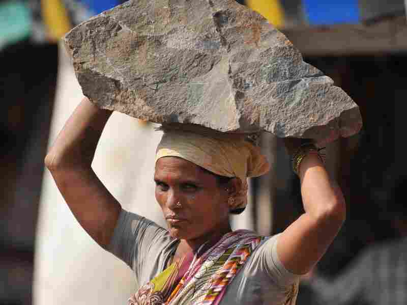 An Indian woman labourer carries a stone on her head at a construction site in Mumbai on Feburary 5, 2011.